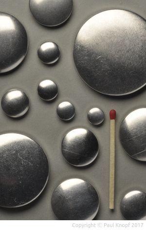 Knopfoberteile in verschiedenen Größen mit einem Streichholz als Maßstab.